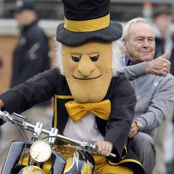 Arnold Palmer rides out with the Wake Forest mascot before the game between the Wake Forest Demon Deacons and the Maryland Terrapins at BB&T Field on October 19, 2013