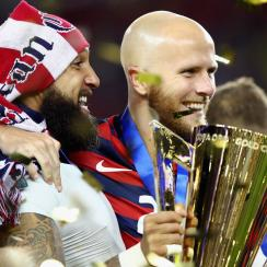 Tim Howard and Michael Bradley carry the USA's Gold Cup trophy