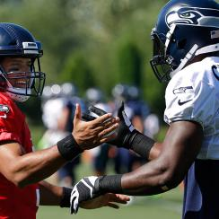 Russell Wilson and Kam Chancellor embrace in a more friendly moment during Tuesday's otherwise testy practice.