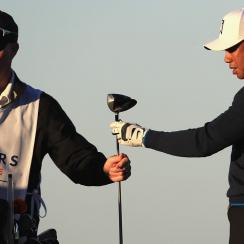 Caddie Joe LaCava hands Tiger Woods a club on the 4th tee during the pro-am round of the Farmers Insurance Open.