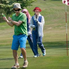 The author works out his swing while the group's caddies look on.