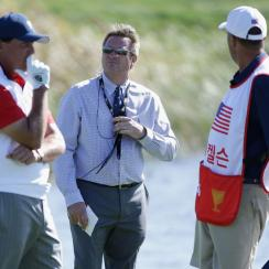 Phil Mickelson confers with his caddie Jim Mackay as rules official Gary Young looks on.