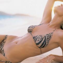 Rebecca Romijn on beach in body-painted version of bikini by Bendigo.