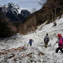 Hikers climbing past avalanche debris near Mount Okuhotaka-dake in the Japanese Alps near Kamikochi, Japan.