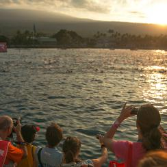 In this photo provided by the 2014 IRONMAN World Championship presented by GoPro, onlookers watch the swimmers at the start of the race on Saturday, Oct. 11, 2014 in Kailua Kona, Hawaii.