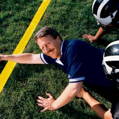 Stan Honey poses on the field holding a football over a computer generated yellow line. Honey founded the company Sportvision, which invented glowing first down lines for professional football and illuminated pucks for professional hockey.