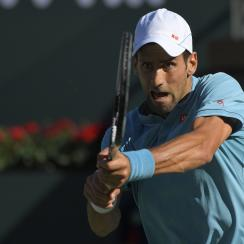 Novak Djokovic, of Serbia, returns a shot to Nick Kyrgios, of Australia, at the BNP Paribas Open tennis tournament, Wednesday, March 15, 2017, in Indian Wells, Calif. (AP Photo/Mark J. Terrill)