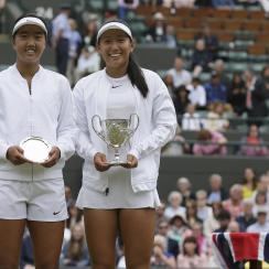 Claire Liu of the United States, center, celebrates with the trophy after beating compatriot Ann Li to win the Girls' Singles final match on day twelve at the Wimbledon Tennis Championships in London Saturday, July 15, 2017. (AP Photo/Tim Ireland)