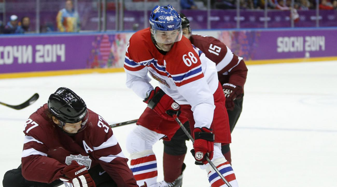 Czech Republic forward Jaromir Jagr battles for the puck in the first period of a men's ice hockey game at the 2014 Winter Olympics.