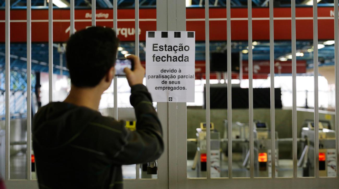 "A commuter snaps a photo of a sign that reads in Portuguese ""Station closed"" at the Arthur Alvim metro station in Sao Paulo, Brazil, where a train strike is cause for concern a week before the World Cup."