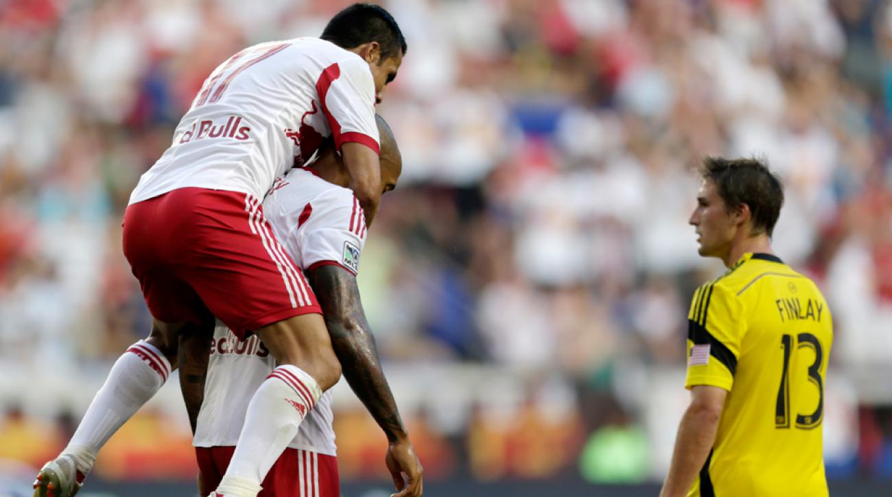 Tim Cahill leaps onto Thierry Henry's back after the latter scores against the Columbus Crew in a 4-1 New York Red Bulls victory on Saturday.