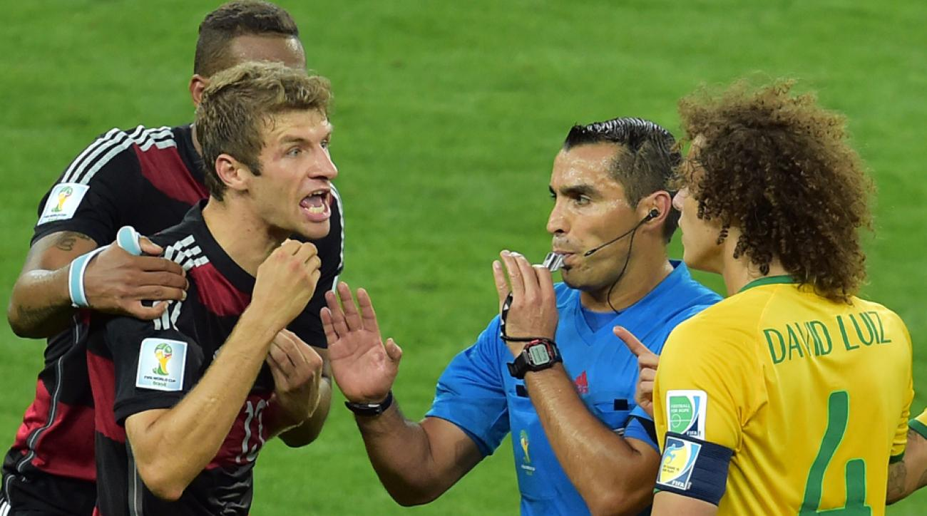 Mexican referee Marco Antonio Rodriguez, center, separates Thomas Muller and David Luiz in the World Cup semifinals.