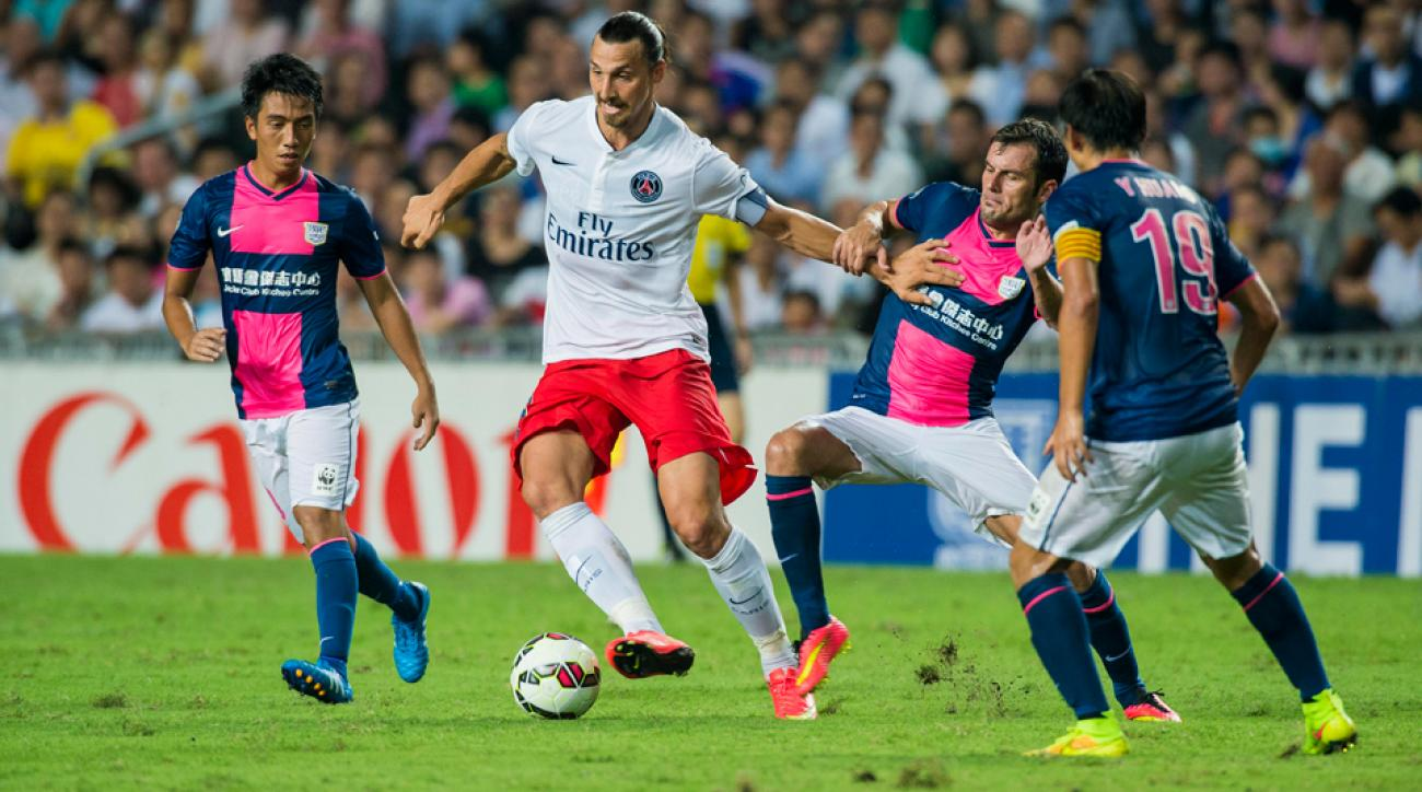 Zlatan Ibrahimovic plays through a trio of Kitchee defenders during PSG's preseason rout on Tuesday.