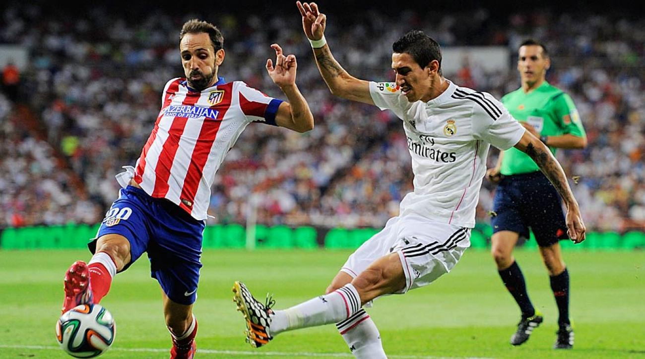 Raul Garcia (left) of Atletico Madrid tries to deflect a ball from Real Madrid's Angel di Maria in the first leg of the Spanish Super Cup.