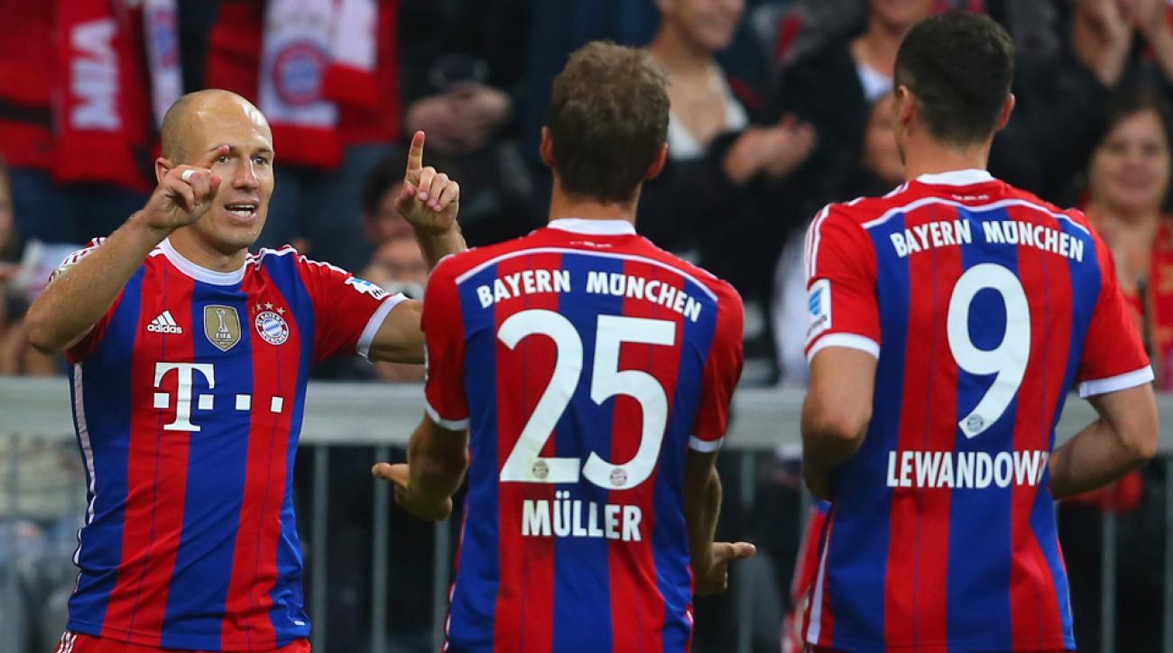 Bayern Munich's Arjen Robben, left, celebrates his goal against Wolfsburg with Thomas Muller and Robert Lewandowski.