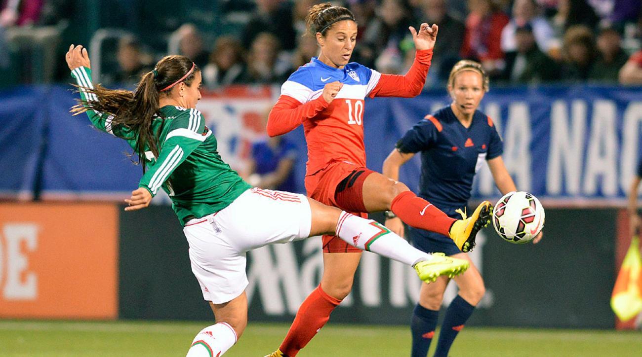 U.S. midfielder Carli Lloyd contends for a ball against Mexico defender Nayeli Rangel.