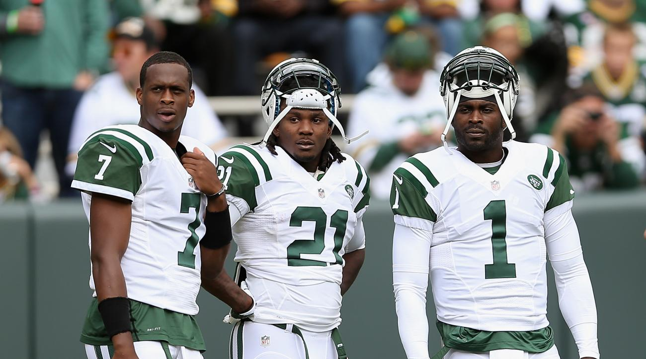 Quarterbacks Geno Smith and Michael Vick stand with running back Chris Johnson before the NFL game against the Green Bay Packers at Lambeau Field on September 14, 2014 in Green Bay, Wisconsin.