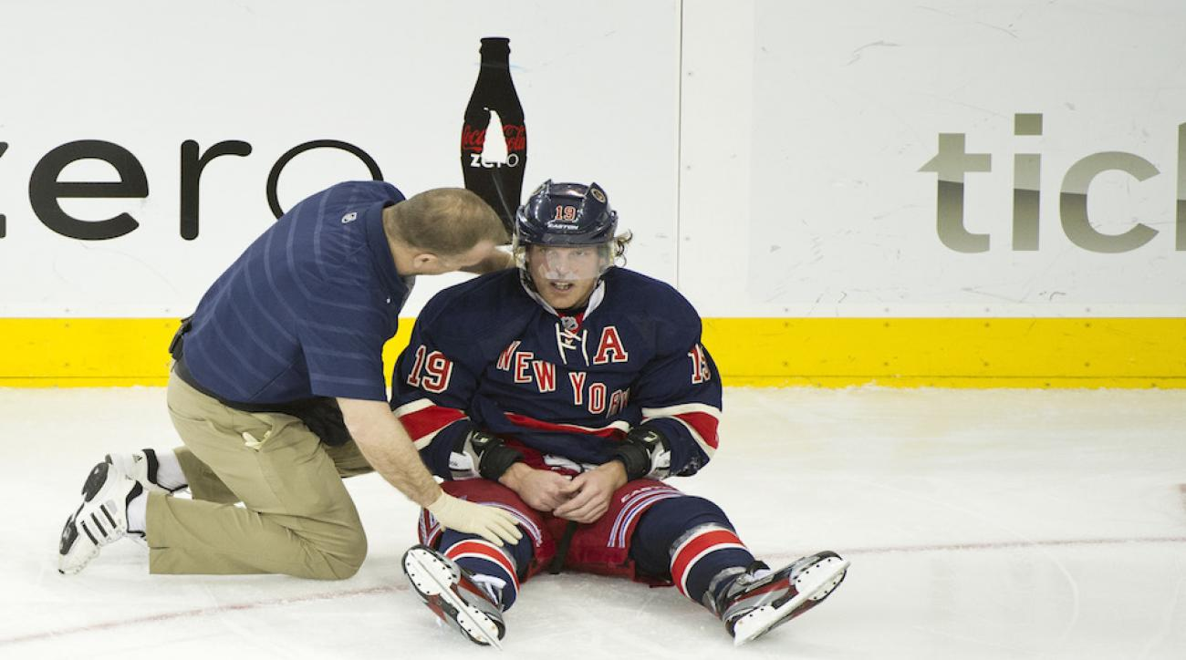 NHL player Brad Richards is examined for concussion symptoms during a 2013 game at Madison Square Garden. A class-action suit leveled against the NHL by Richards' peers alleges the league has not done enough to warn players of the danger of concussions