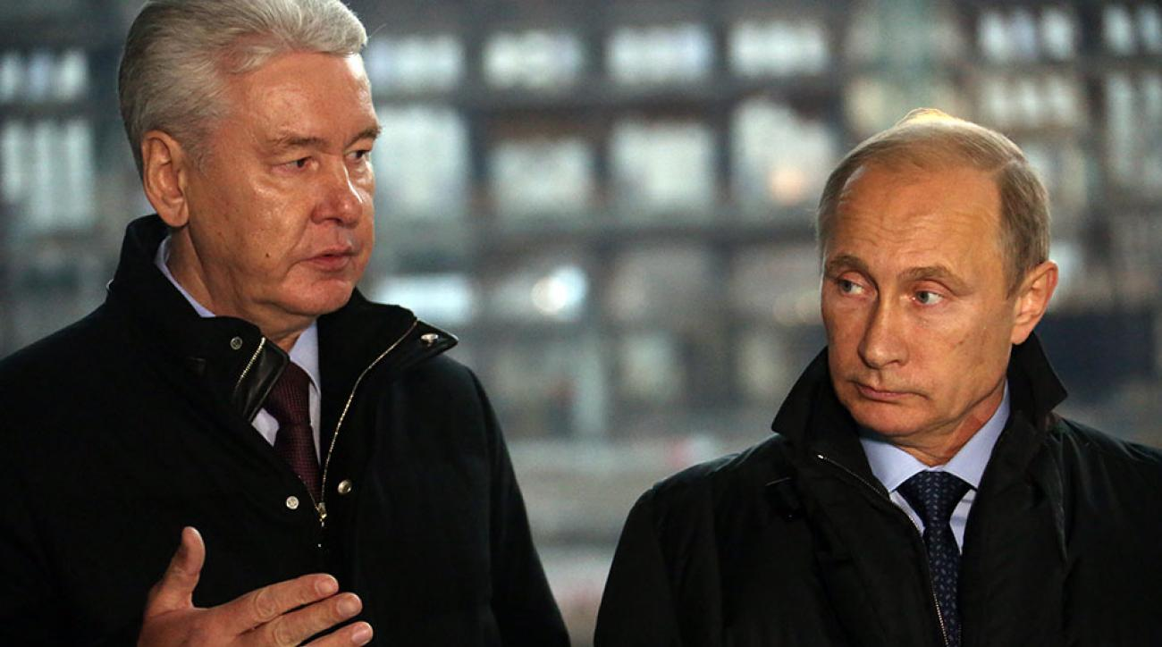Russian President Vladimir Putin (R) and Moscow's Mayor Sergei Sobyanin (L) observe a reconstruction site of the Luzhniki stadium