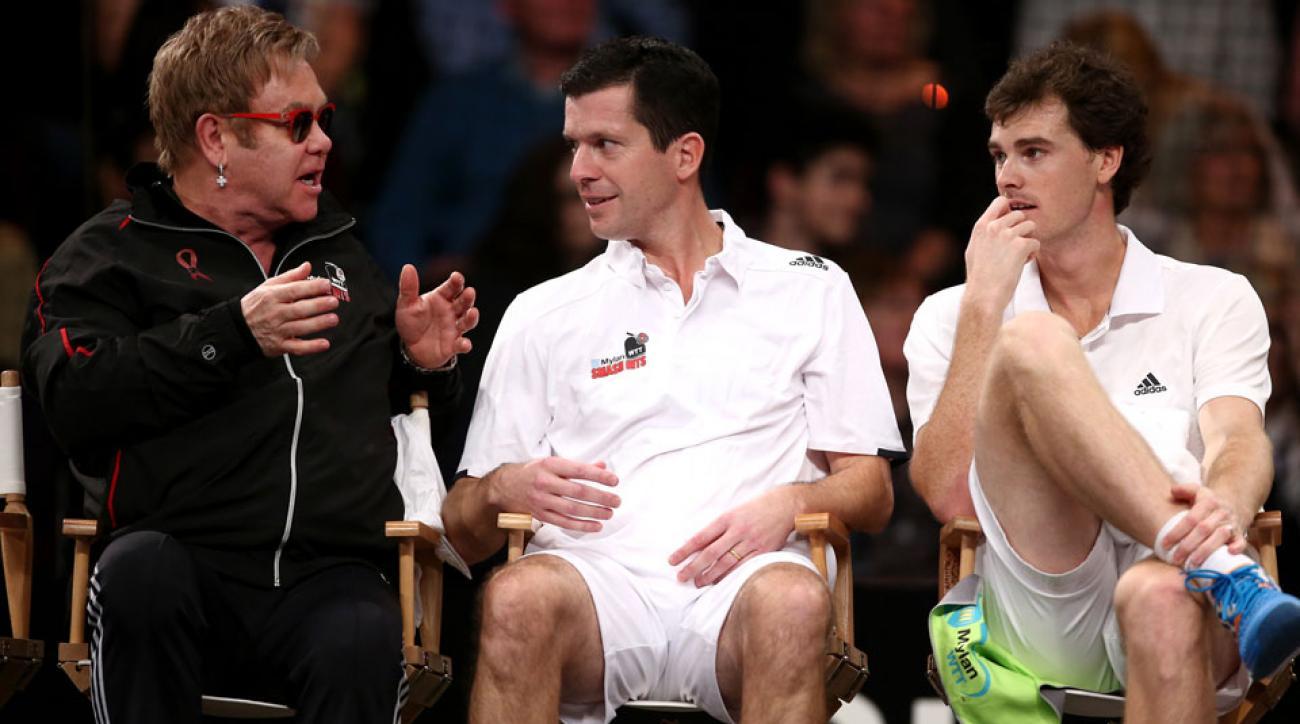 Sir Elton John (L) talks to Tim Henman (C) and Jamie Murray (R)