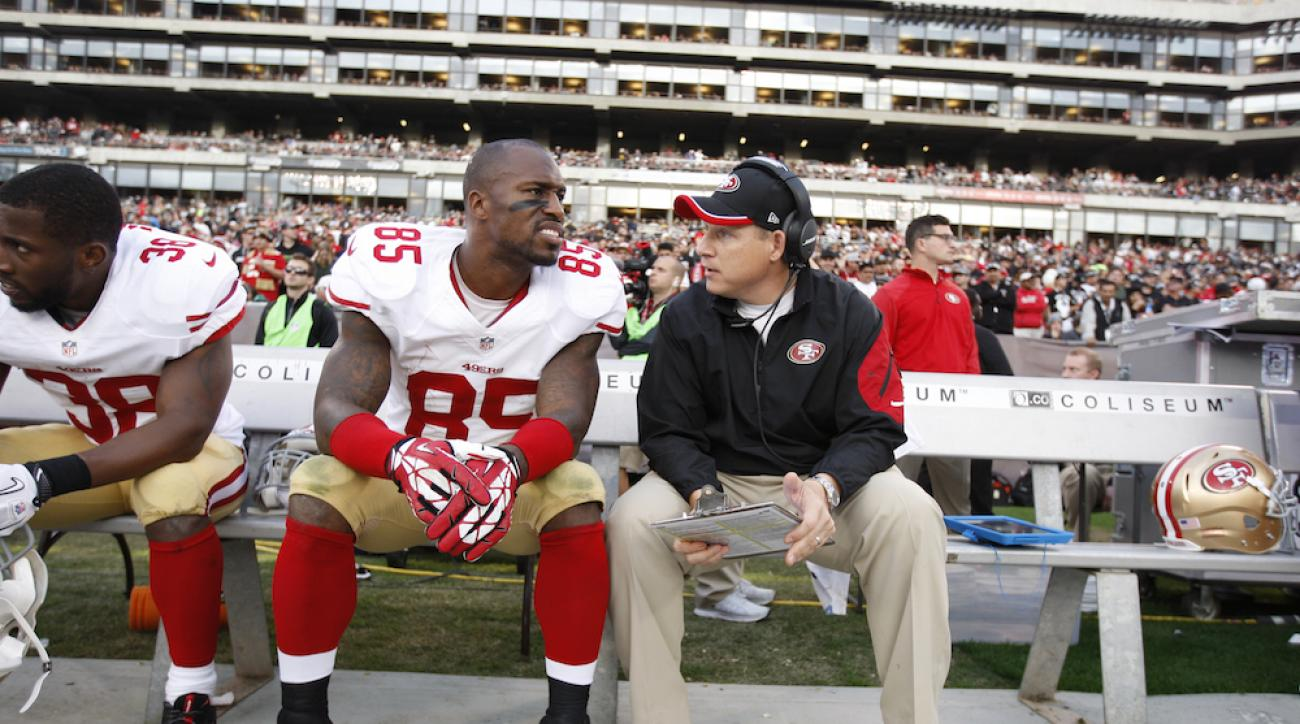Eric Mangini coaches Vernon Davis on the sideline. Manigni is being considered for the San Francisco 49ers' defensive coordinator job.