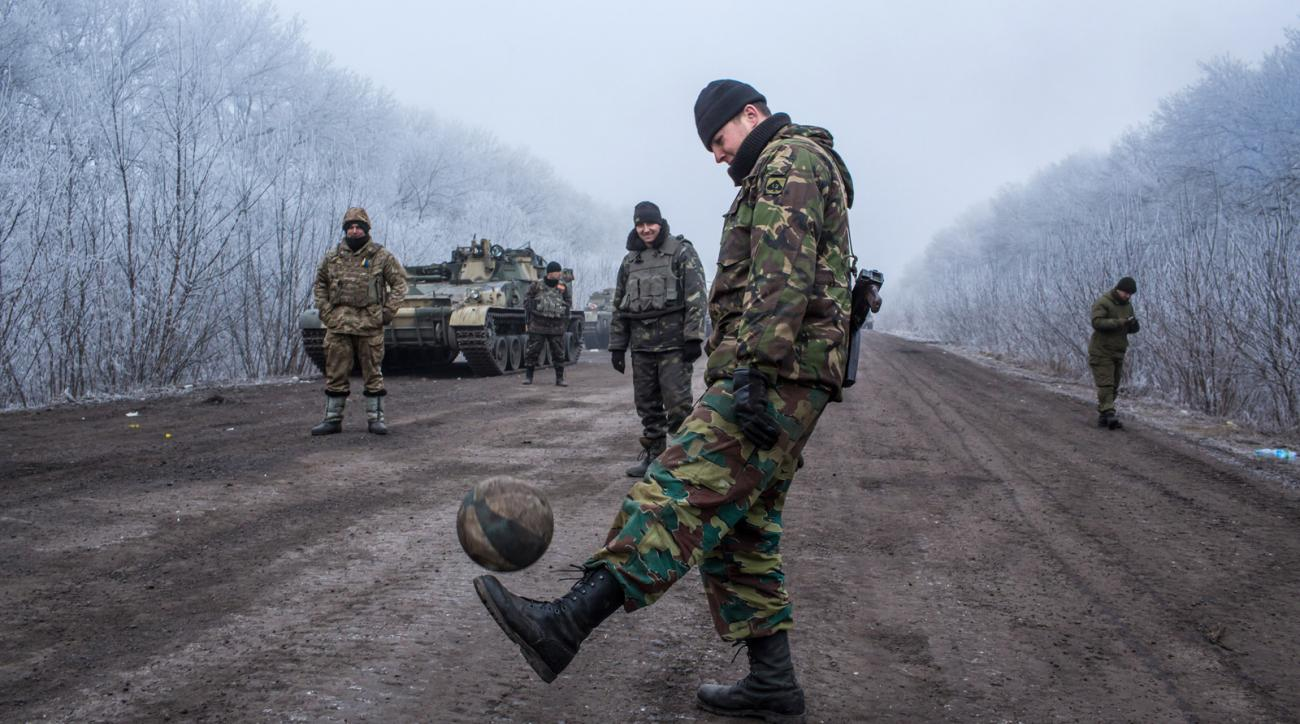 Ukrainian soldiers play football on the road leading to the embattled town of Debaltseve on February 15, 2015 outside Artemivsk, Ukraine.