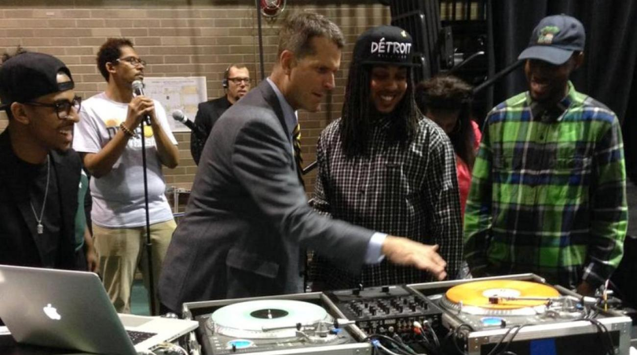 Michigan's Jim Harbaugh jumps behind the turntables