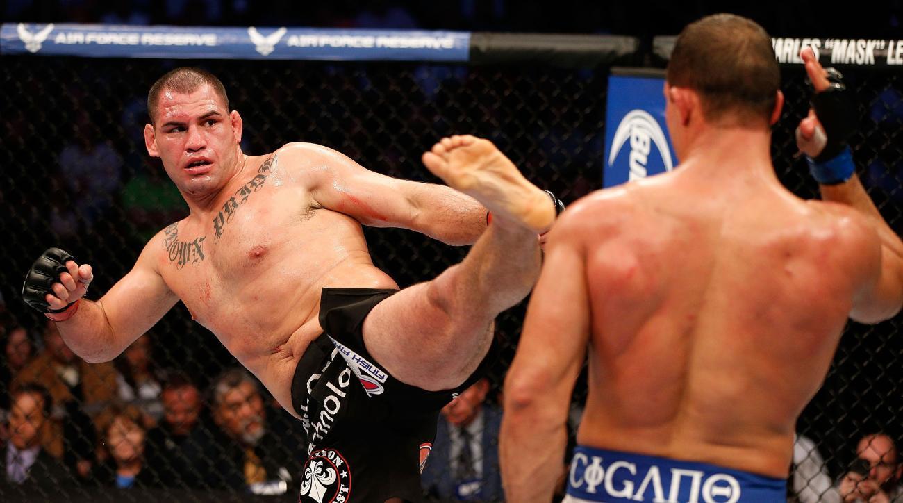 Cain Velasquez kicks Junior Dos Santos in their UFC heavyweight championship fight in 2013.