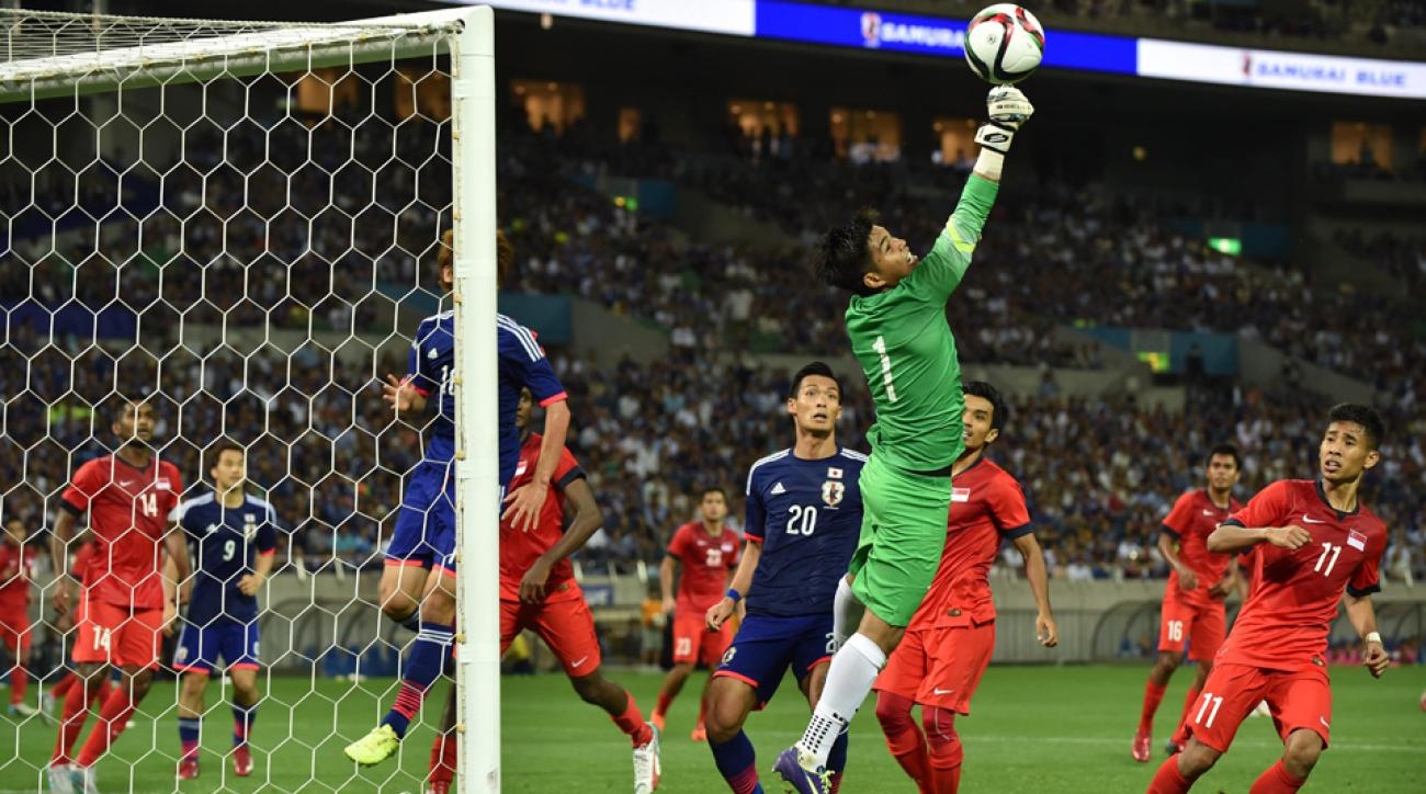 Singapore goalkeeper Mohamad Izwan Bin Mahbud punches the ball away in a shock 0-0 draw with Japan in a World Cup qualifying match.