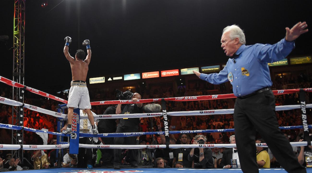 Jessie Vargas, left, celebrates thinking that he won Sunday's interim WBO world title fight against Timothy Bradley after referee Patrick Russell (right) prematurely ended the fight.