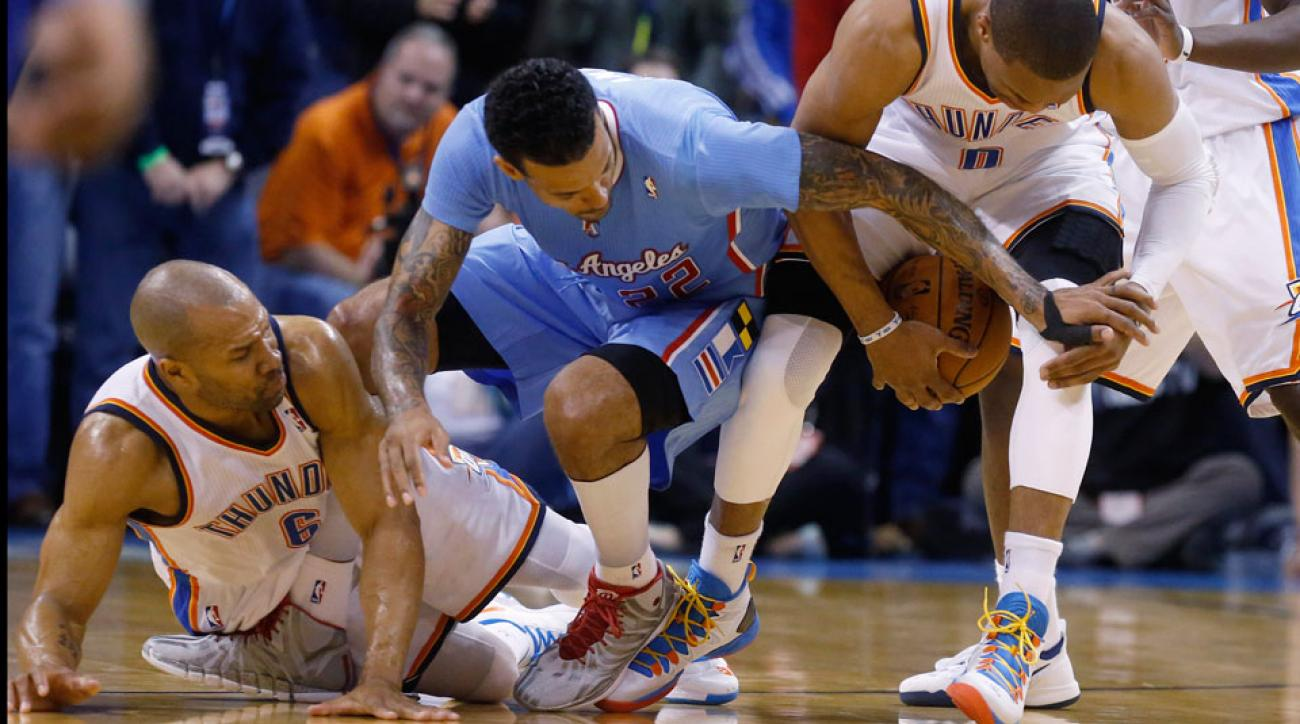 Derek Fisher and Matt Barnes fight for a loose ball with Russell Westbrook during a Feb. 23, 2014, game between the Clippers and Thunder.