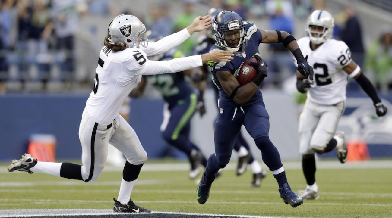 Former Oakland Raiders punter Chris Kluwe tries to make a tackle on a punt returner during a 2013 game against the Seattle Seahawks.