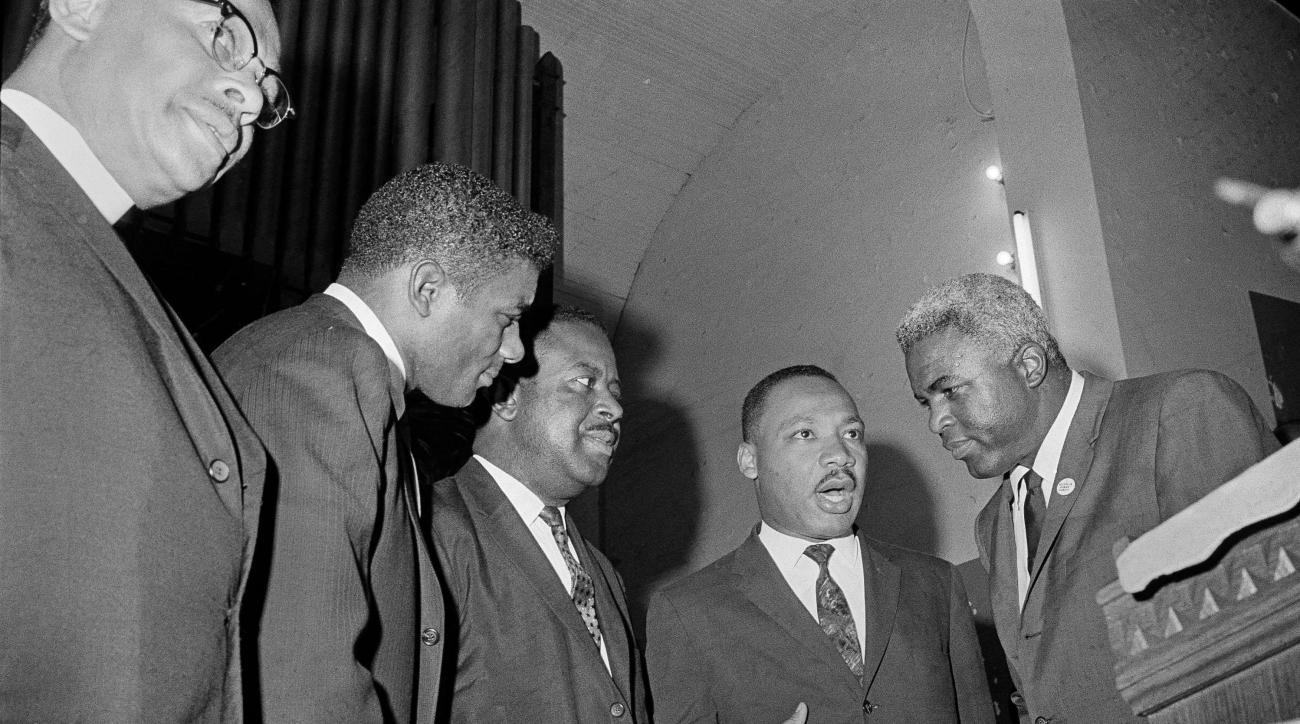 Martin Luther King Jr., second from right, is shown with baseball player Jackie Robinson, far right, and boxer Floyd Patterson, far left.