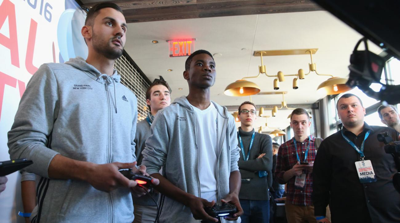 Demetri Anastasiou, left, competes in the FIFA Interactive World Cup. SI's Stanley Kay, third from right, watches on intently, scouting his future opponent.