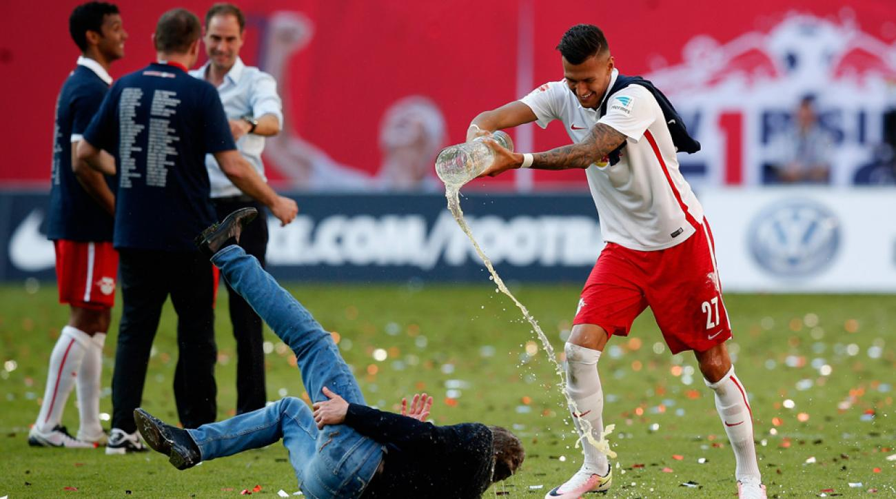 Red Bull Leipzig manager Ralf Rangnick injures hamstring running away from a beer shower