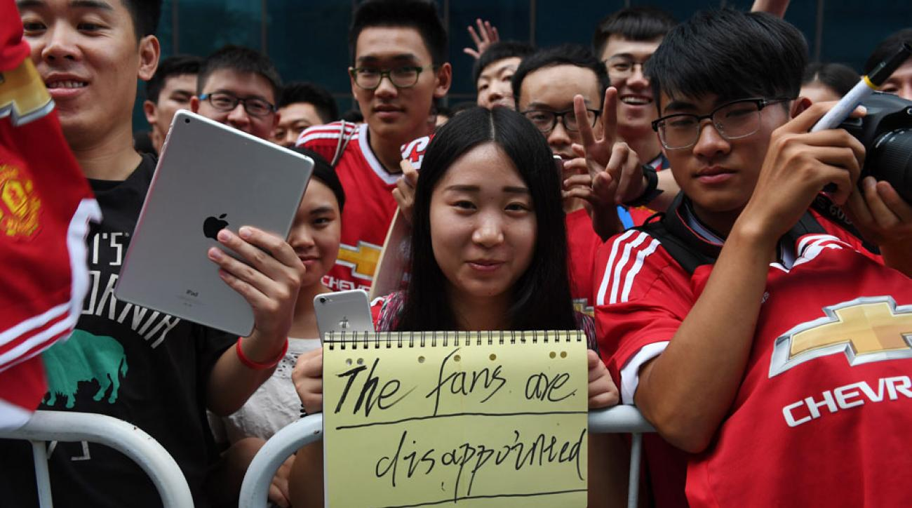 Manchester United fans in China stand outside the team hotel