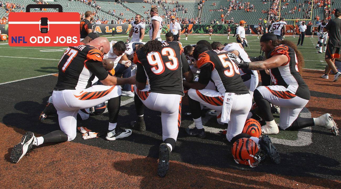 Bengals team chaplain LaMorris Crawford works with Andy Dalton, Marvin Lewis