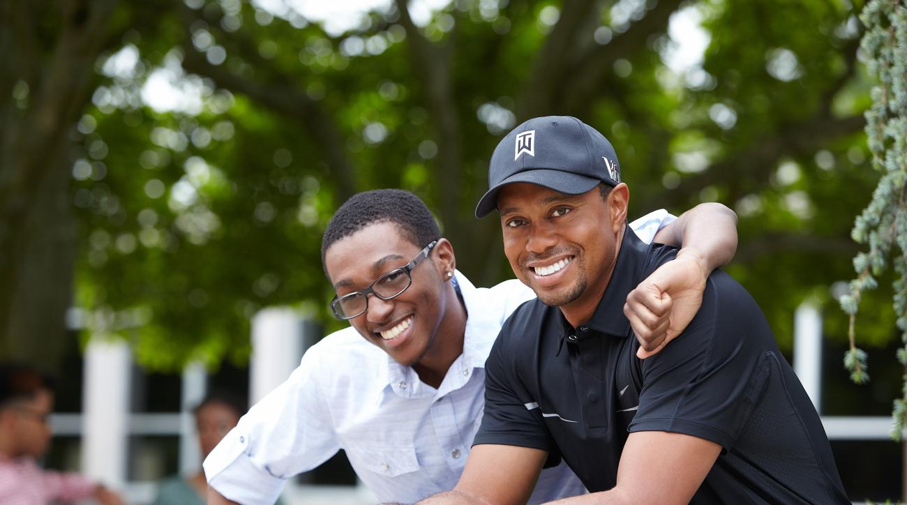Marcus Edwards, a Tiger Woods Foundation alum, and Tiger Woods pose for a photo in 2013.