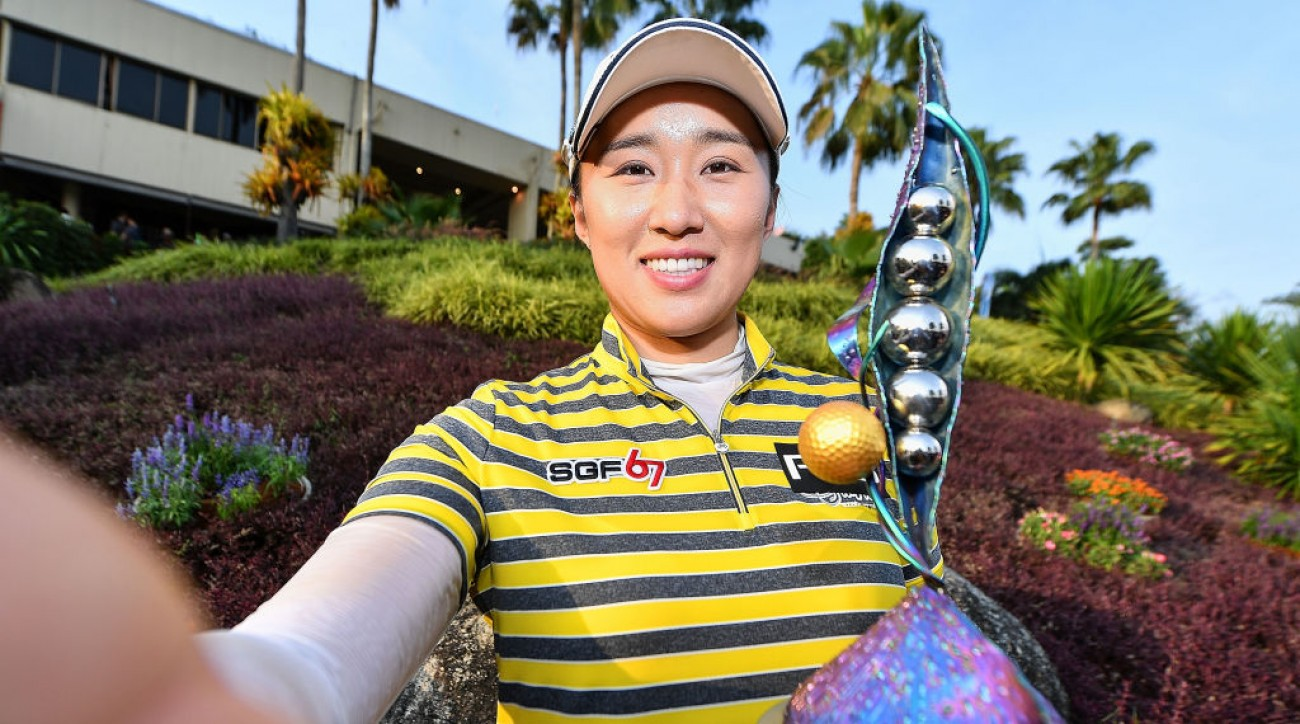 Amy Yang imitates taking a selfie photo with her trophy after winning the Honda LPGA Thailand.