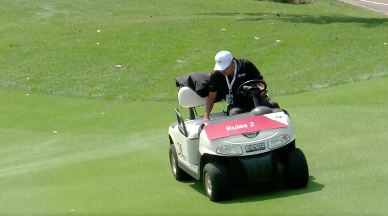 A rules official looks for a golf ball in his cart.