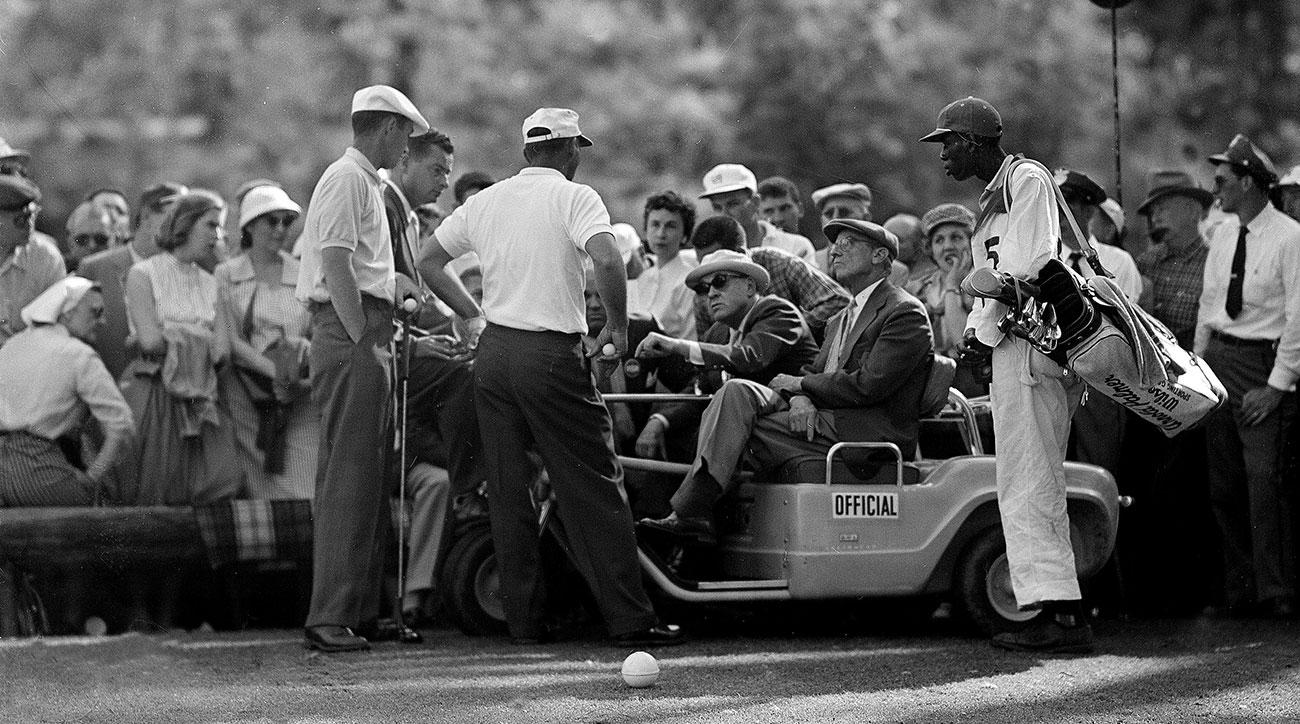 Arnold Palmer, center standing, argues a rules point at the 12th hole after his ball became embedded in the mud during final round of the 1958 Masters. Ken Venturi stands to his left.