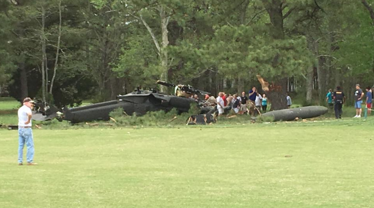 Neighbors, onlookers inspect the crash scene of a military helicopter that killed one crew member and injured others Monday afternoon.