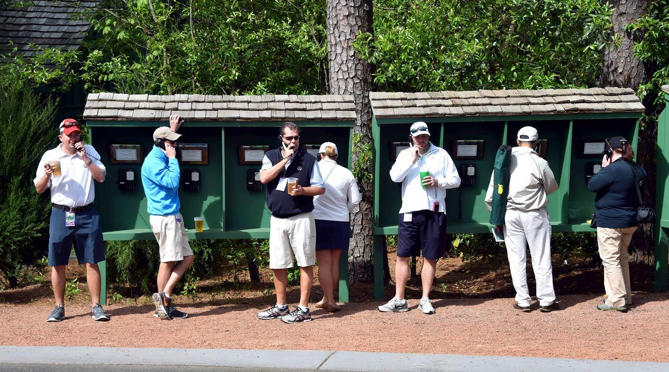 Patrons make phone calls during a practice round prior to the start of the 2017 Masters.