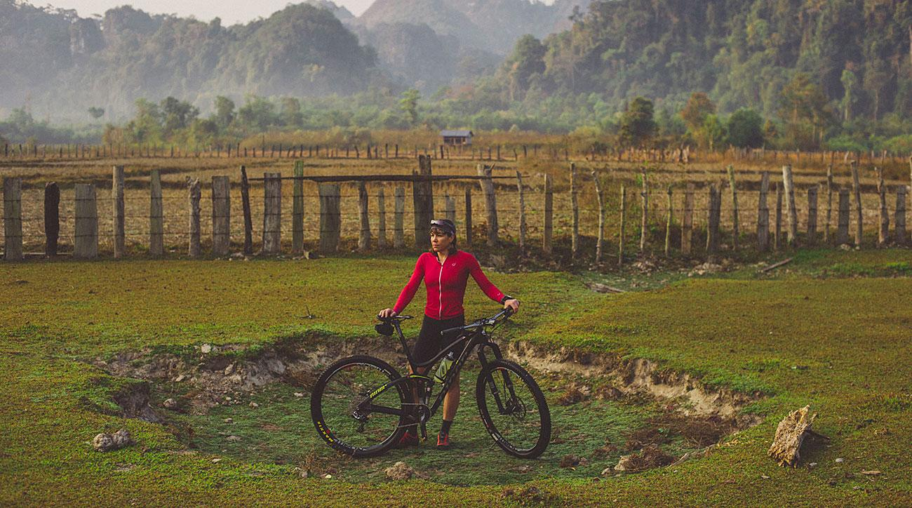 Rebecca standing with her bike in a bomb crater in Laos.