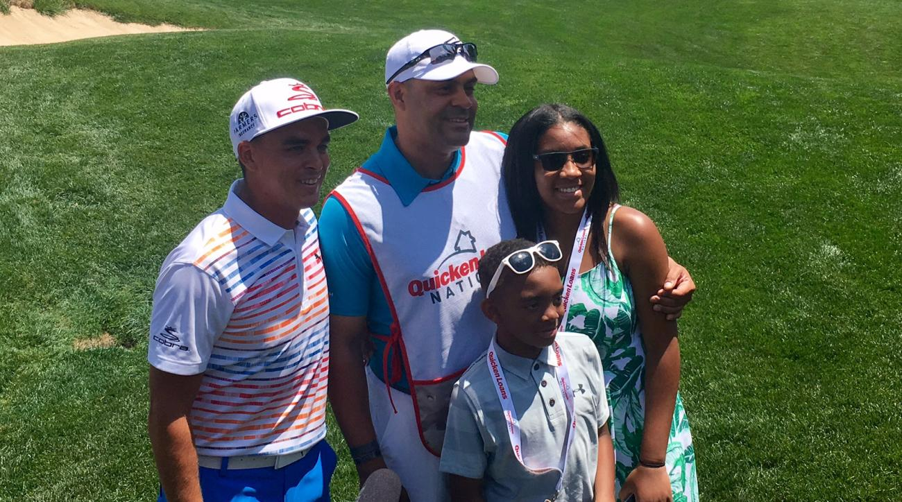Rickie Fowler with a serviceman and his family at the Quicken Loans National pro-am.