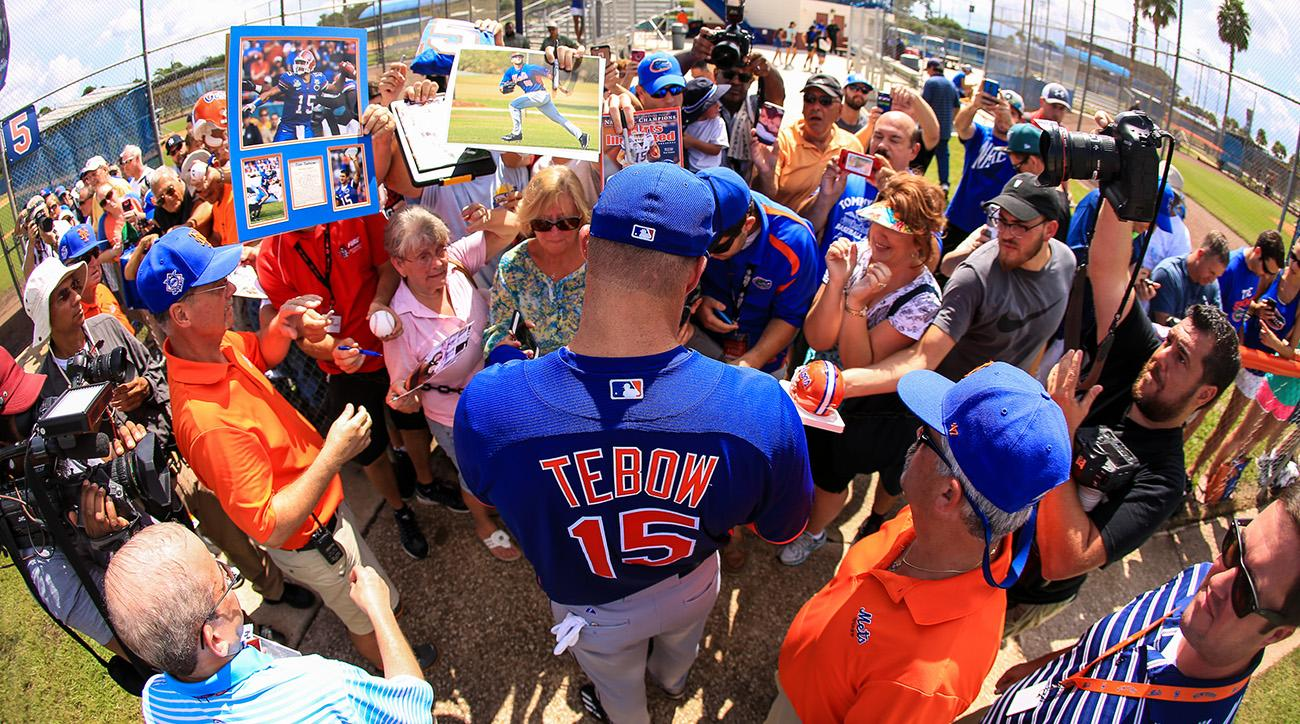 Tebow signs autographs after a media session last September.