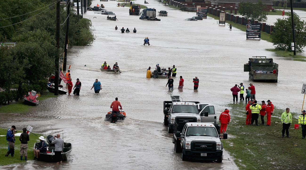 People attempt to make their way out of a flooded neighborhood in Houston, Texas.