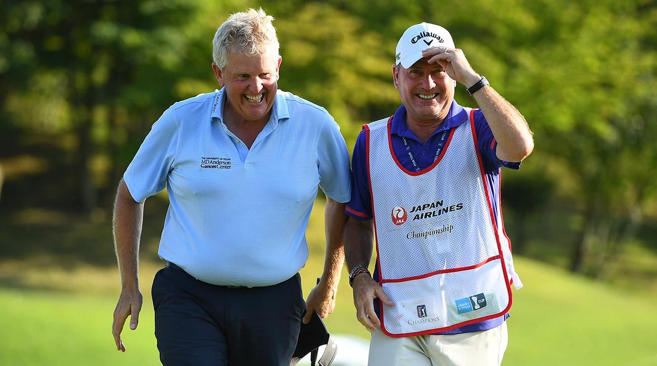 Colin Montgomerie celebrates with his caddie after making his putt on the 18th green during the final round of the Japan Airlines Championship.