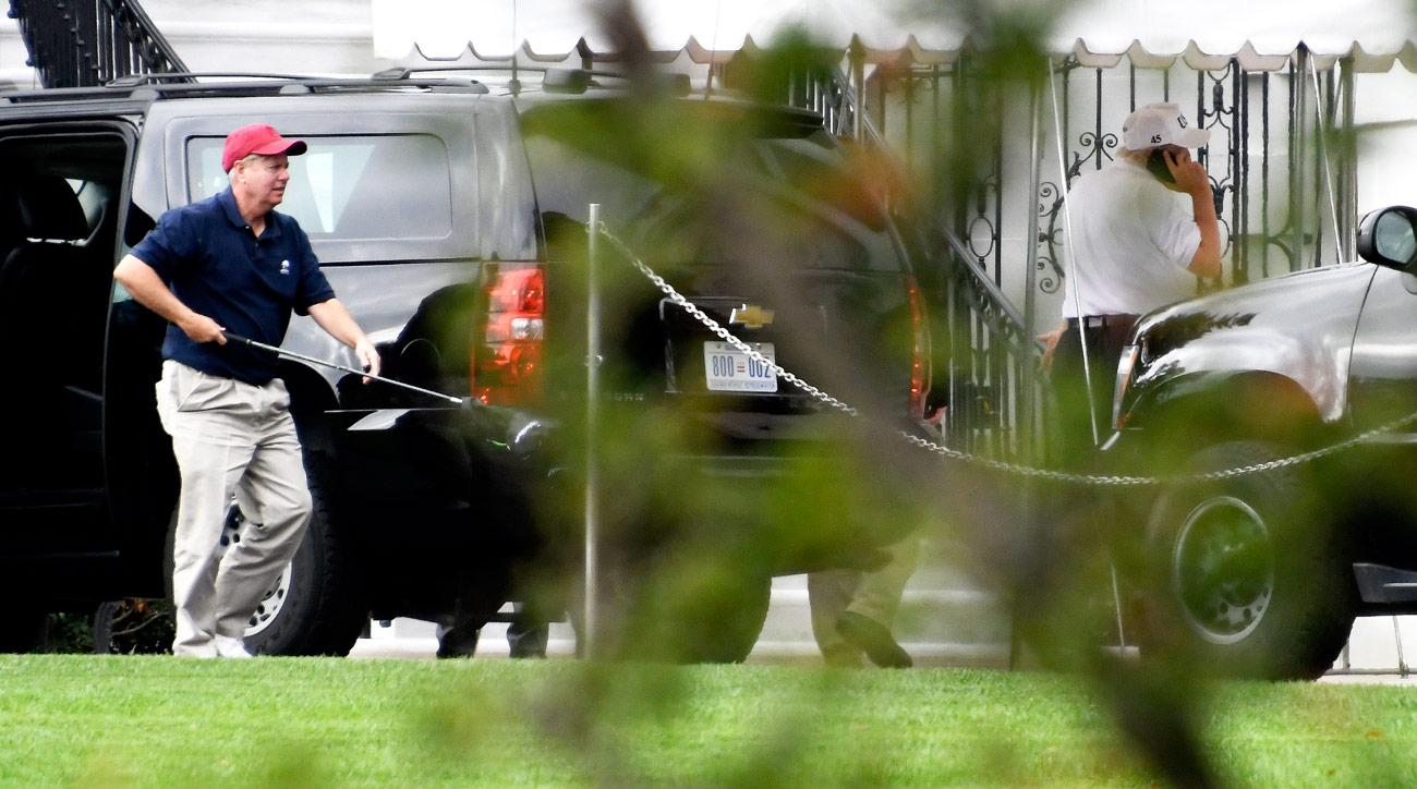 Senator Lindsey Graham (R-SC), left, carries one of his golf clubs as he leaves the presidential limo at the White House on October 14, 2017 in Washington, DC. U.S. President Donald Trump is seen at right talking on the phone. The two are returning after playing a round of golf.