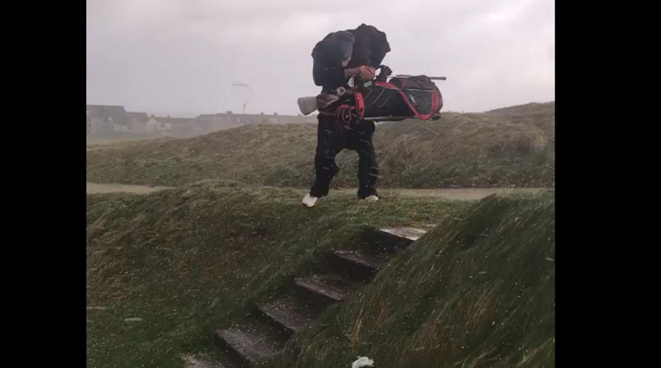 A golfer battles high winds and hail at Newquay Golf Club in Newquay, Cornwall.